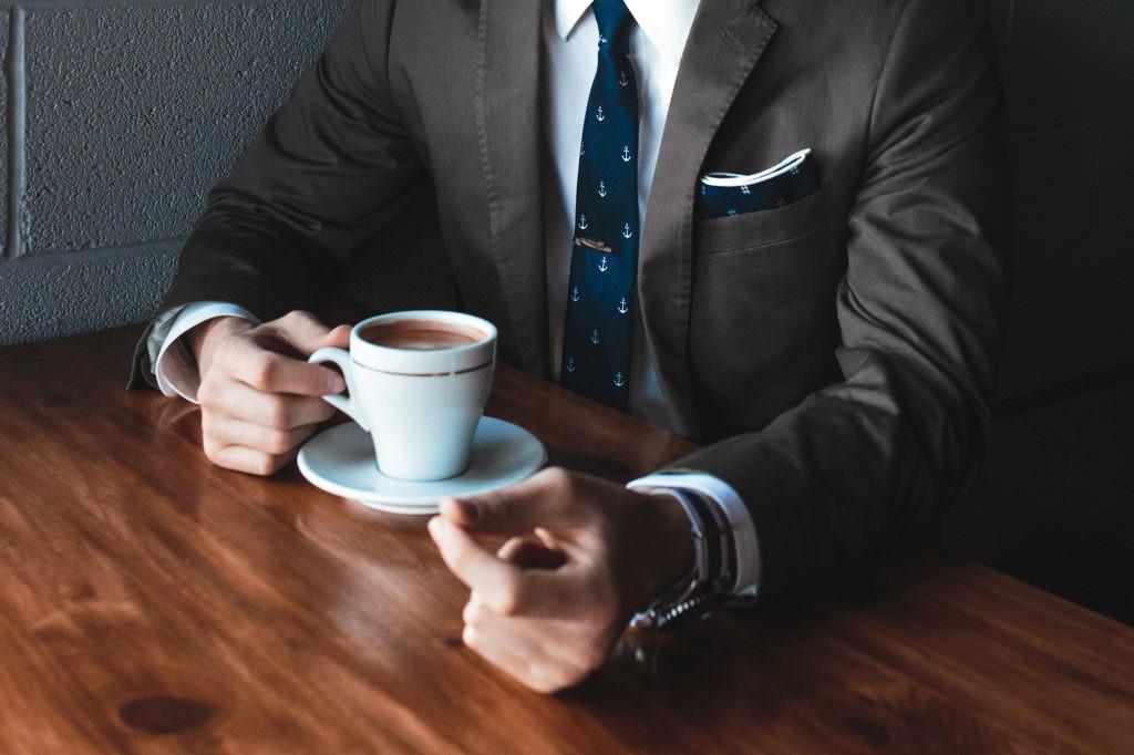 Mann im Anzug mit Kaffee